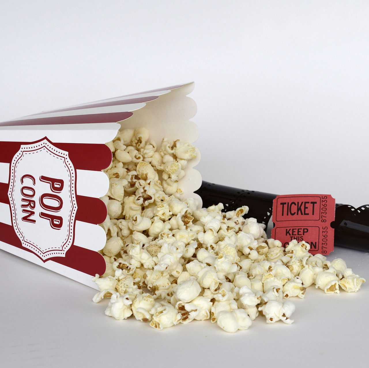 image of popcorn a theatre ticket and a film roll for movies reviews by thatbhaumikgirl