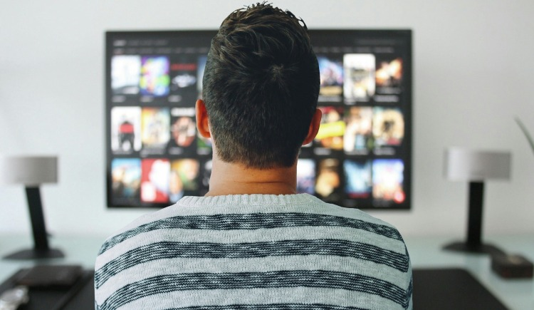 image of a person looking at the TV implying that this section leads to TV & Web Series Reviews